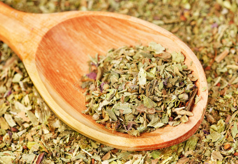 Pile of ground dried Basil (Sweet Basil) as background with wooden spoon. Used as a spice in culinary herb all over the world. The plant is also used in stock photos