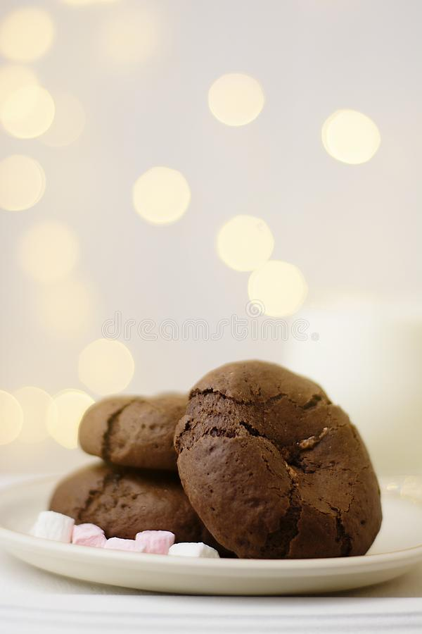 A pile of handcrafted chocolate cookies. Natural handmade snakes for healthy breakfast. Christmas festive lights on background royalty free stock image