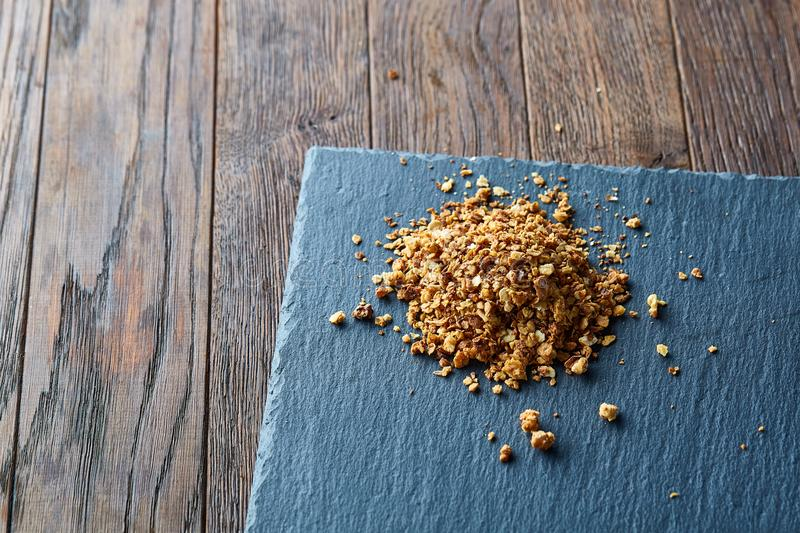 Pile of healthy granola on black stony board over vintage wooden background, top view, close-up, selective focus royalty free stock photo