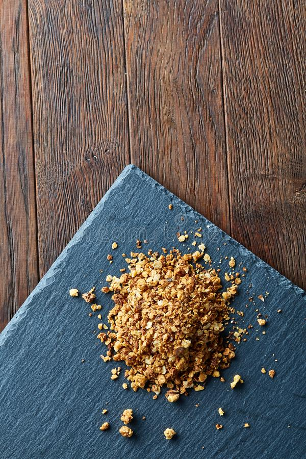 Pile of healthy granola on black stony board over vintage wooden background, top view, close-up, selective focus stock image