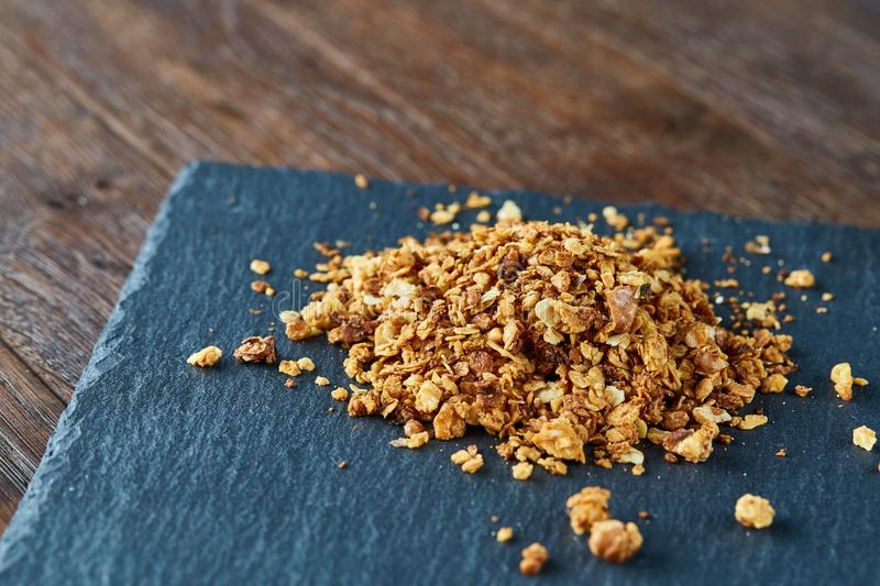 Pile of healthy granola on black stony board over vintage wooden background, top view, close-up, selective focus stock photos