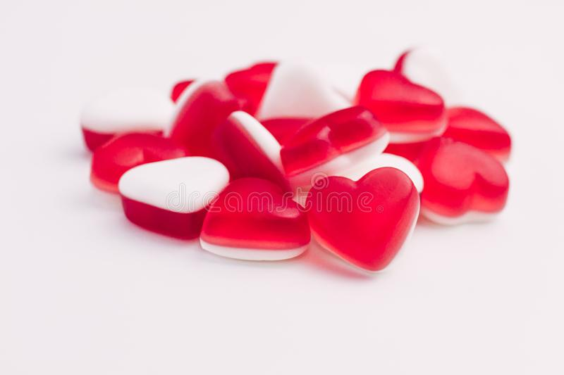 Pile of heart shaped red and white jelly sweets on white background. Place for text. Pile of heart shaped red and white jelly sweets on white background for royalty free stock photo