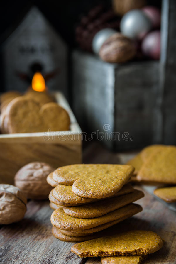 Pile of home baked Christmas gingerbread cookies in wood box, burning candle, pine cones and colorful baubles, rustic kitchen stock images