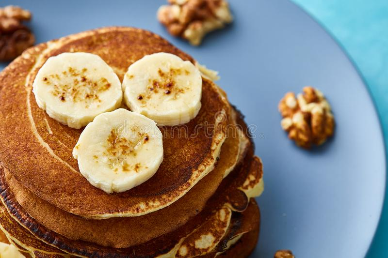 Pile of homemade pancakes with banana and walnuts on blue background, selective focus stock photos