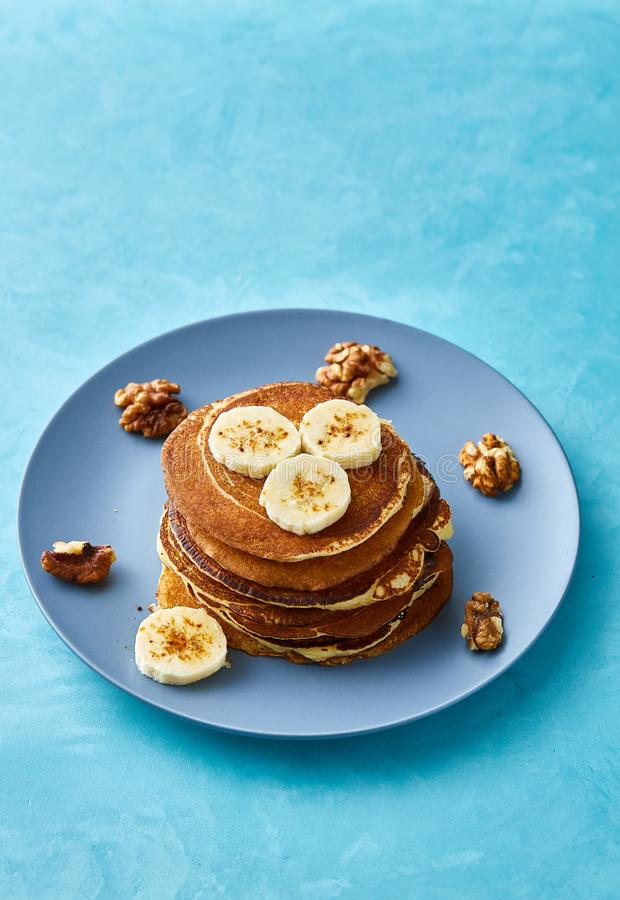 Pile of homemade pancakes with banana and walnuts on blue background, selective focus royalty free stock photo