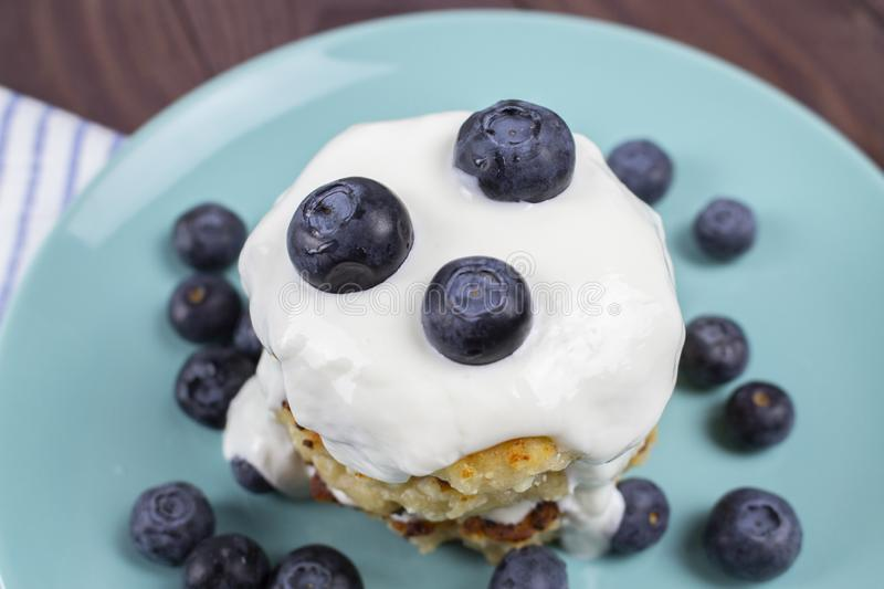 Pile of homemade pancakes with blueberries and sour cream sauce. Homemade cheese pancakes stock photo