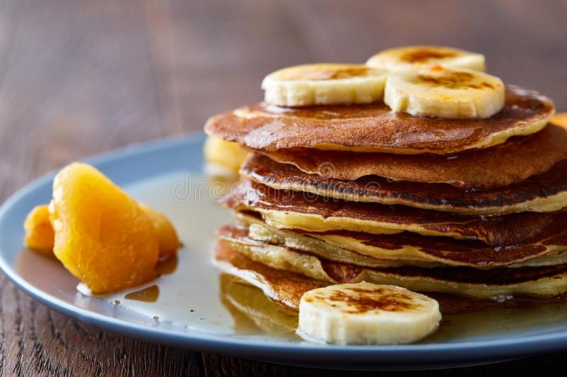 Pile of homemade pancakes with honey and walnuts on rustic wooden background, selective focus. Homemade pancakes with honey, apricot and walnuts on blueish plate royalty free stock photography