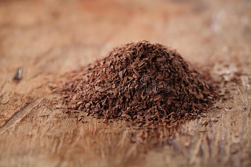 Pile of hot chocolate flakes on wooden background. Shallow DOF stock image