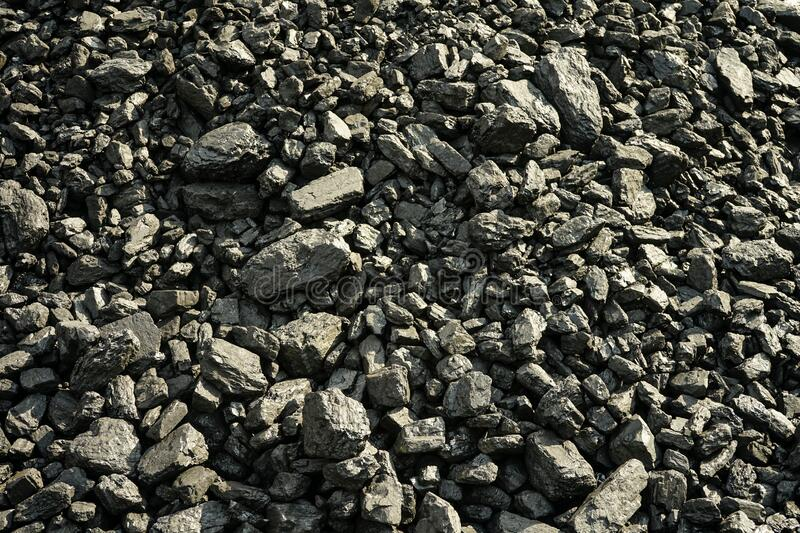 Pile of industrial coal and a train. Fuel and power generation, nature pollution theme. Pile of industrial coal. Fuel and power generation, nature pollution royalty free stock images