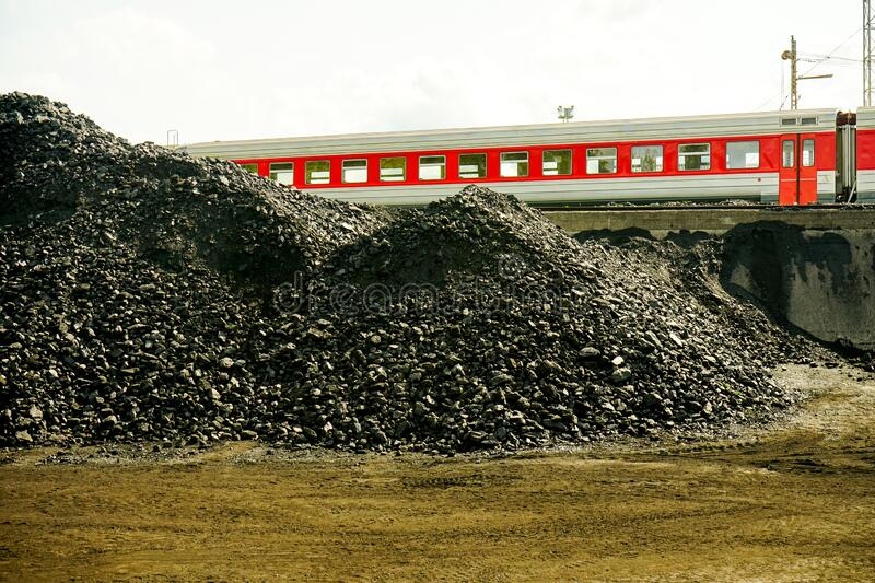 Pile of industrial coal and a train. Fuel and power generation, nature pollution theme. Sustainable traveling stock images