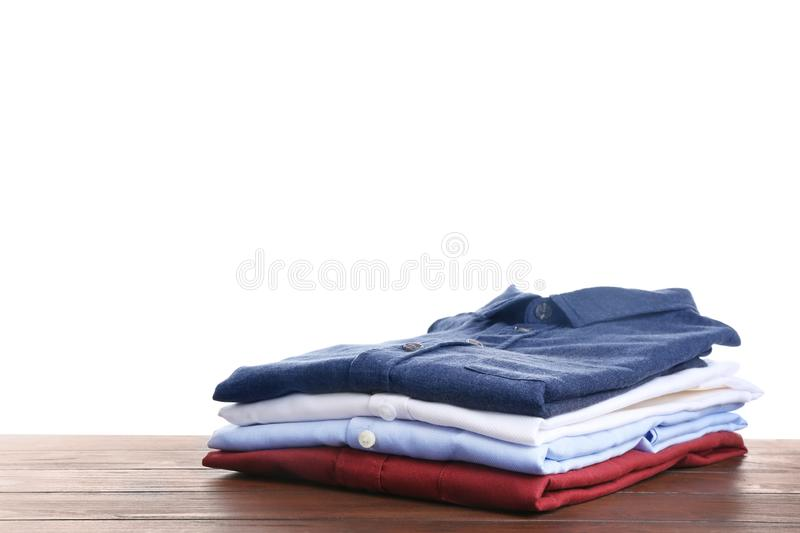Pile of ironed clothes on table against white. Background stock images