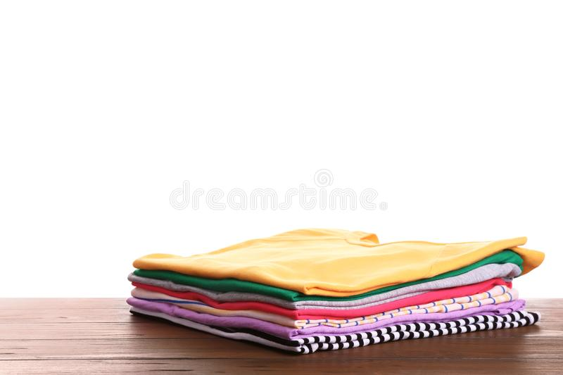 Pile of ironed clothes on table. Against white background stock photo