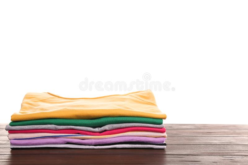 Pile of ironed clothes on table. Space for text. Pile of ironed clothes on table against white background. Space for text stock photos