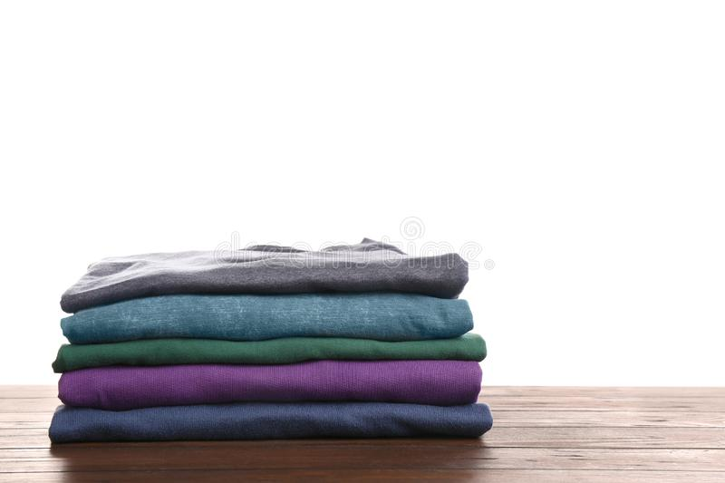 Pile of ironed clothes on table against white background. Space for text royalty free stock photo