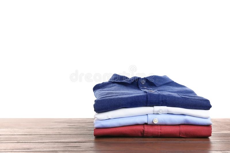 Pile of ironed clothes on table against white background. Space for text stock photo