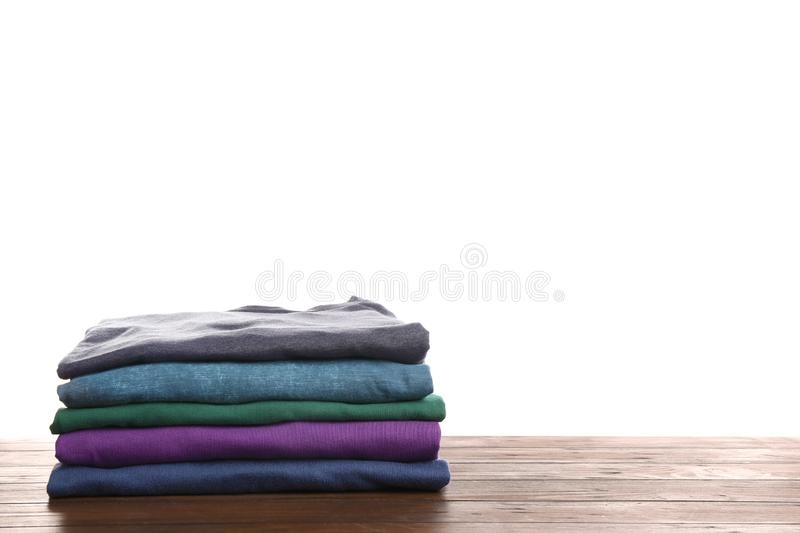 Pile of ironed clothes on table against white background. Space for text stock images