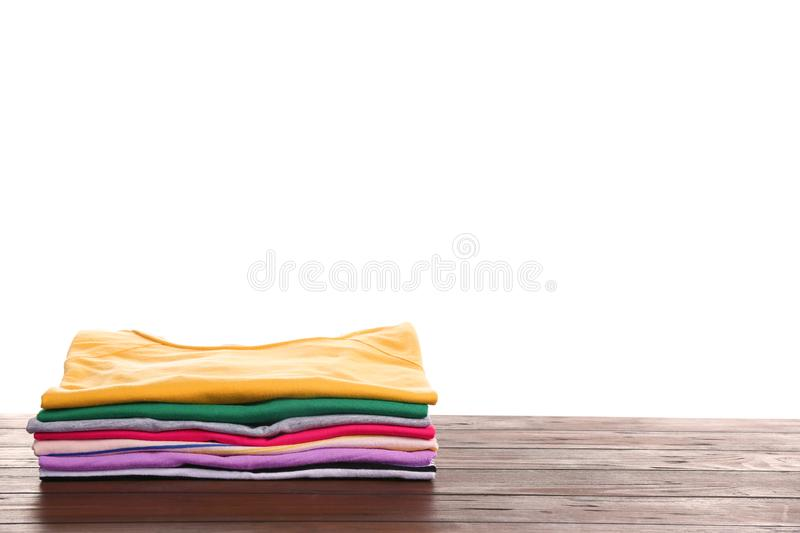 Pile of ironed clothes on table against white background. Space for text royalty free stock photos