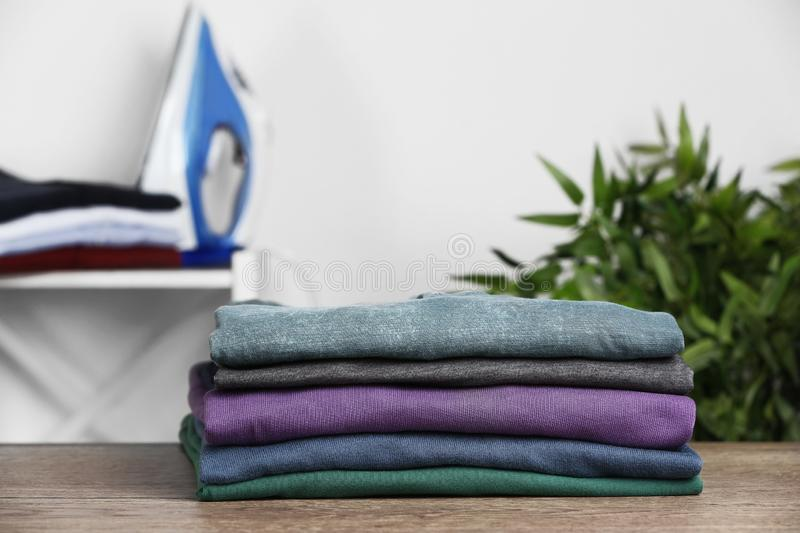 Pile of ironed clothes on table in room. Space for text royalty free stock photo
