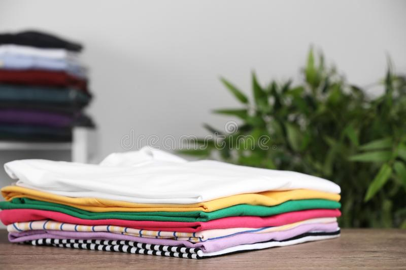 Pile of ironed clothes on table in room. Space for text stock images