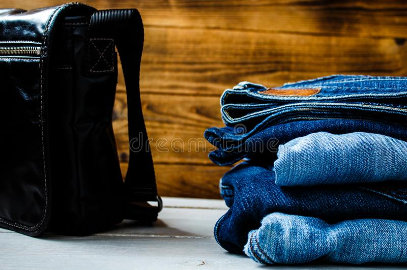 Pile of jeans and bag on a wooden background stock photography