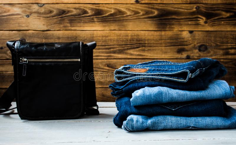 Pile of jeans and bag on a wooden background royalty free stock photography