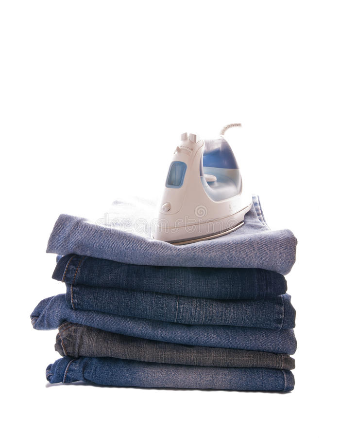 Pile of jeans and an iron stock photography