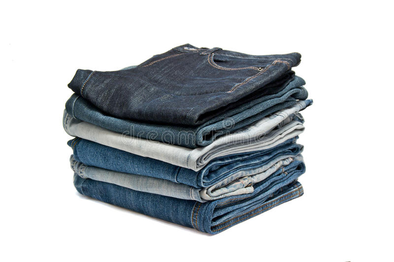 A pile of jeans on a white background. Flat pile of jeans on a white background royalty free stock photography
