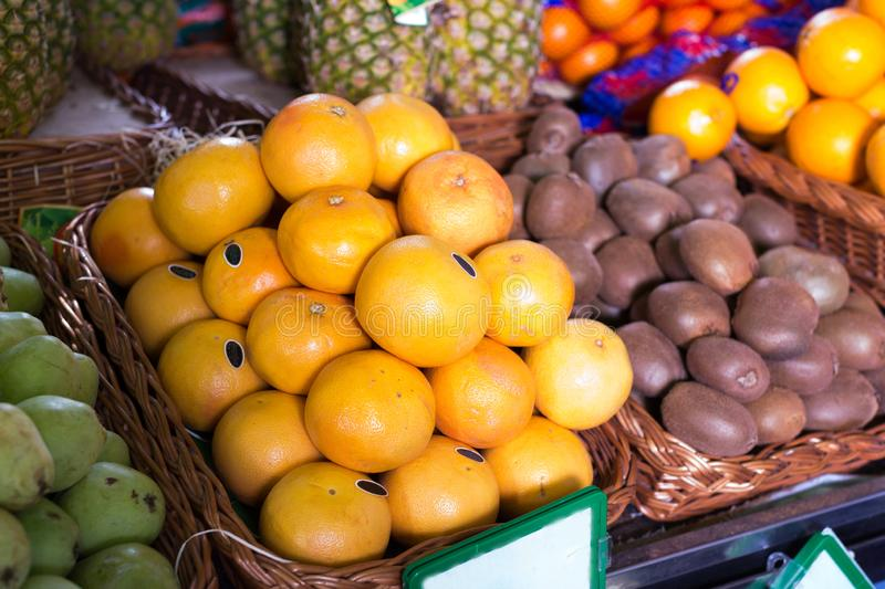 Pile of juicy oranges in wicker baskets on market counter royalty free stock photography