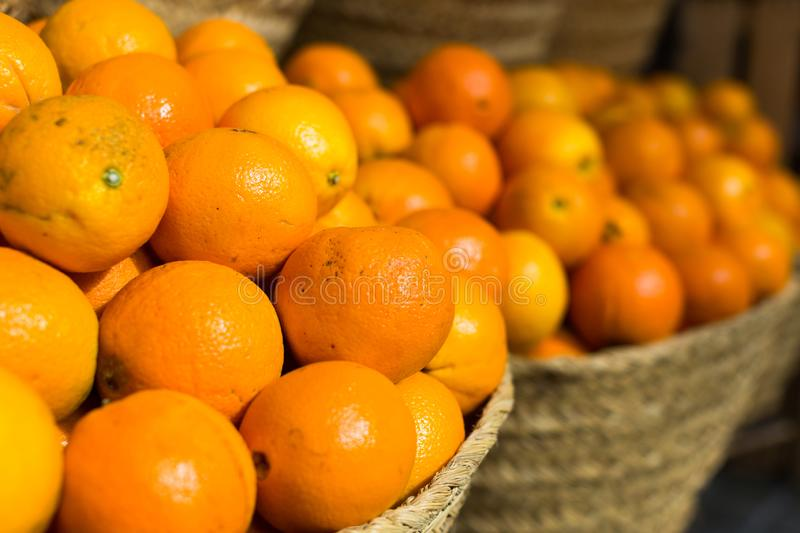Pile of juicy oranges in wicker baskets on market counter stock images