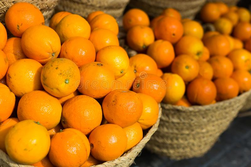 Pile of juicy oranges in wicker baskets on market counter stock image