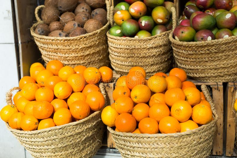 Pile of juicy oranges in wicker baskets on market counter royalty free stock images