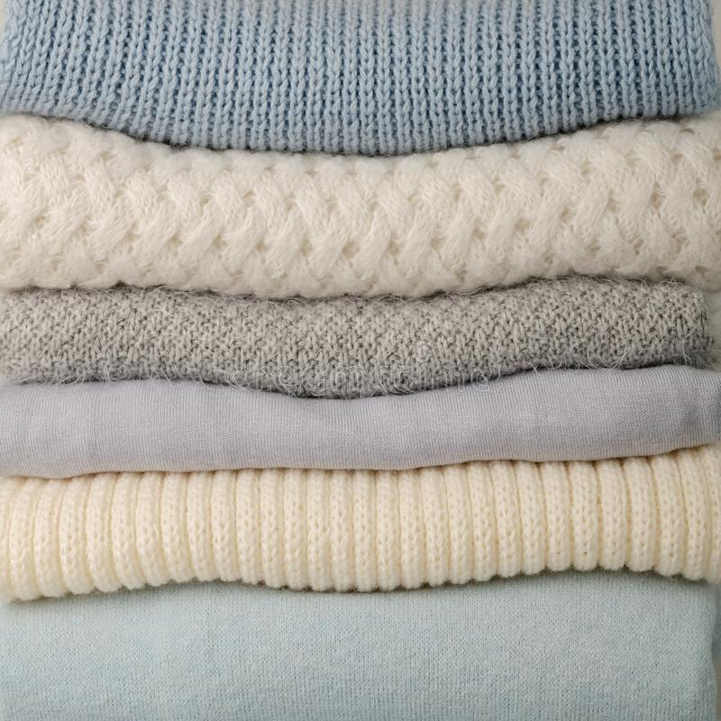 Pile of knitted clothes sweaters, scarves, pullovers blue, whi stock photo