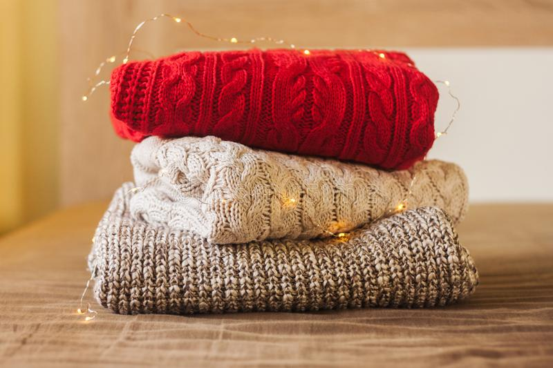 A pile of warm sweaters on the wood bed decorated with lights. A pile of knitted sweaters on the wood bed decorated with lights. Warm comfortable clothes royalty free stock images