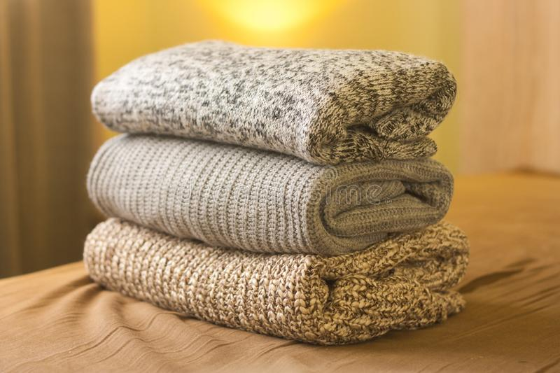 A pile of warm winter autumn sweaters on the wood bed. A pile of knitted winter or autumn sweaters on the wood bed. Warm comfortable clothes stock photography