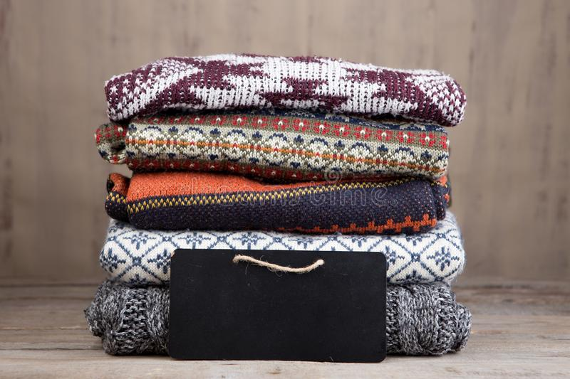Pile of knitted winter sweaters on wooden background royalty free stock photography
