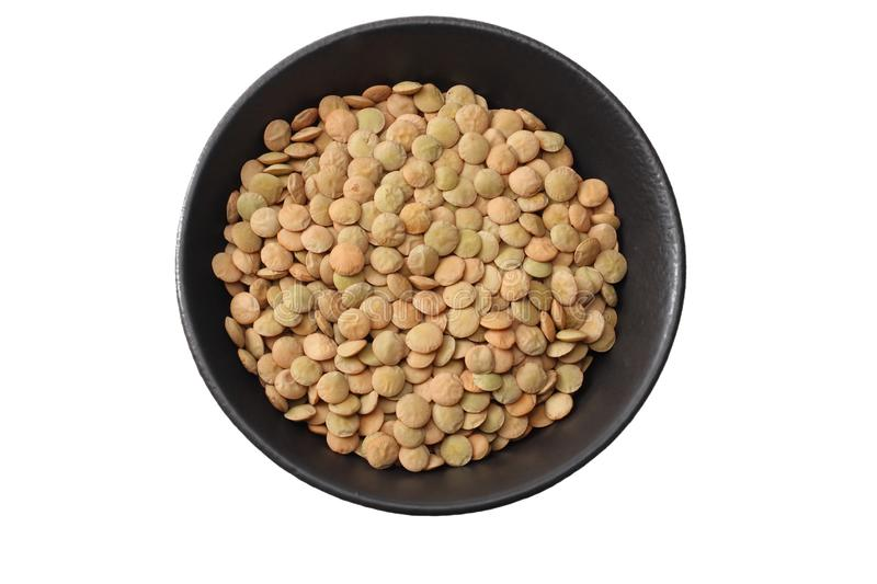 Pile lentil in black bowl isolated on white background. Top view stock photo