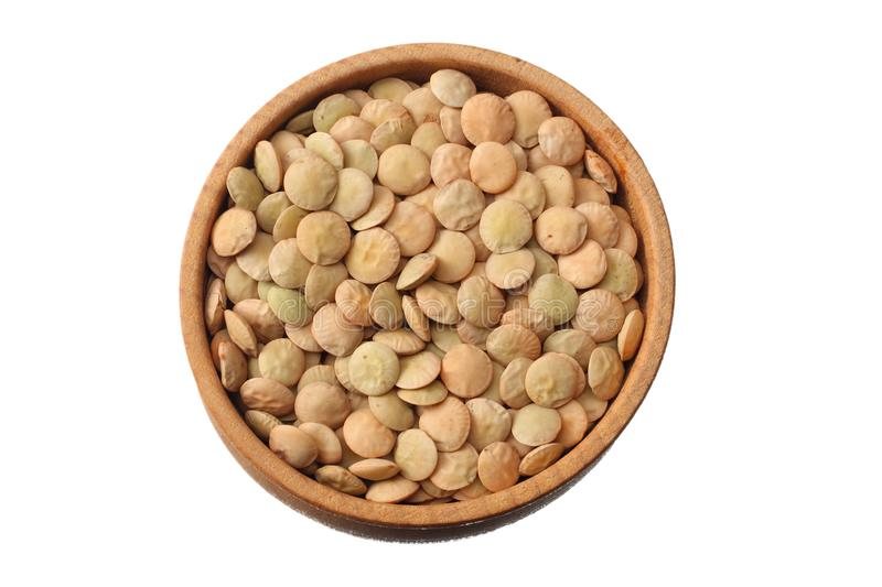 Pile lentil in wooden bowl isolated on white background. Top view royalty free stock photography