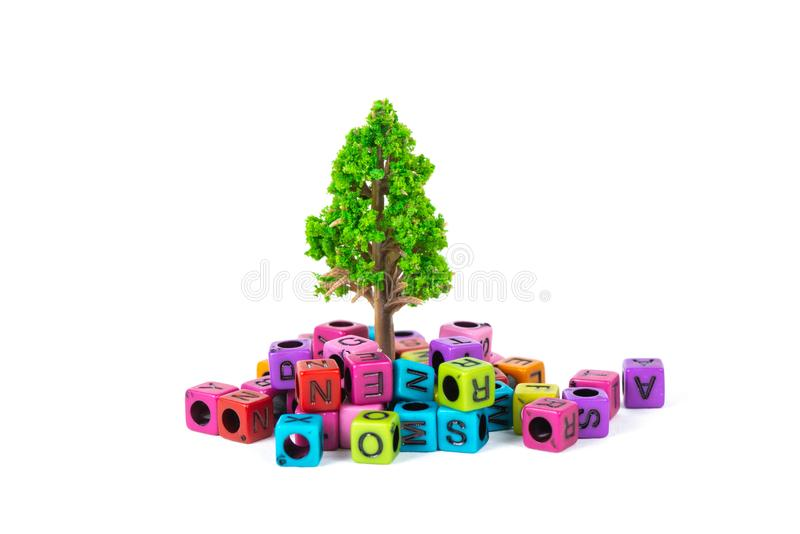 Pile of letter bead or beads with alphabet and little tree on white background. Pile of beads or letter bead with alphabet and little tree on white background royalty free stock images