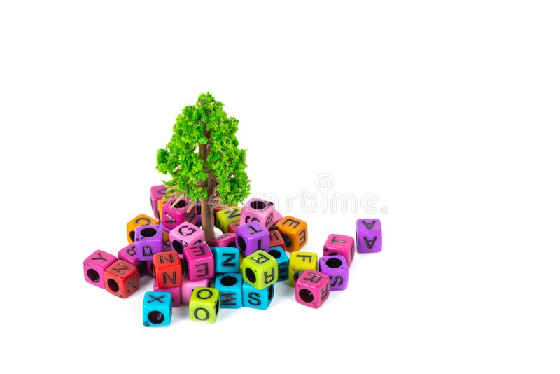 Pile of letter bead or beads with alphabet and little tree on white background. Pile of beads or letter bead with alphabet and little tree on white background stock images
