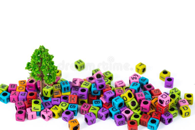 Pile of letter bead or beads with alphabet and little tree on white background. Pile of beads or letter bead with alphabet and little tree on white background stock photography