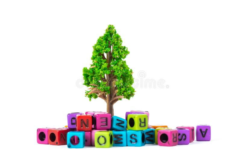 Pile of letter bead or beads with alphabet and little tree on white background. Pile of beads or letter bead with alphabet and little tree on white background royalty free stock image