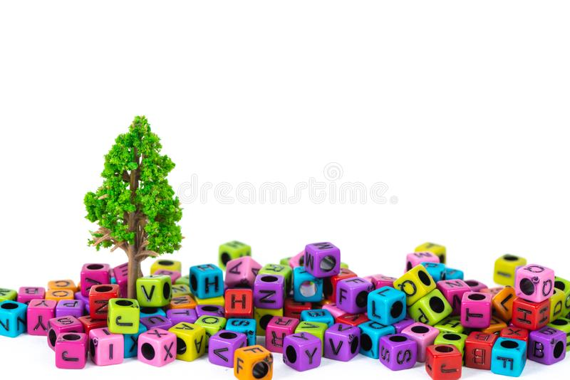 Pile of letter bead or beads with alphabet and little tree on white background. Pile of beads or letter bead with alphabet and little tree on white background stock photos