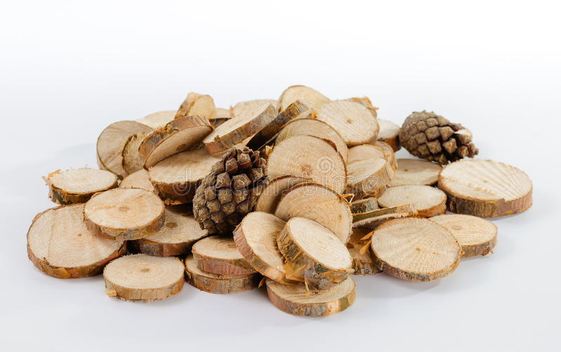 Pile of little round pieces of sawn pine branches and pine cones. On white background royalty free stock images