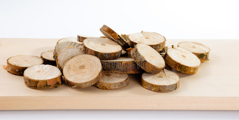 Pile of little round pieces of sawn pine branches on wooden plan. K on white background royalty free stock photography