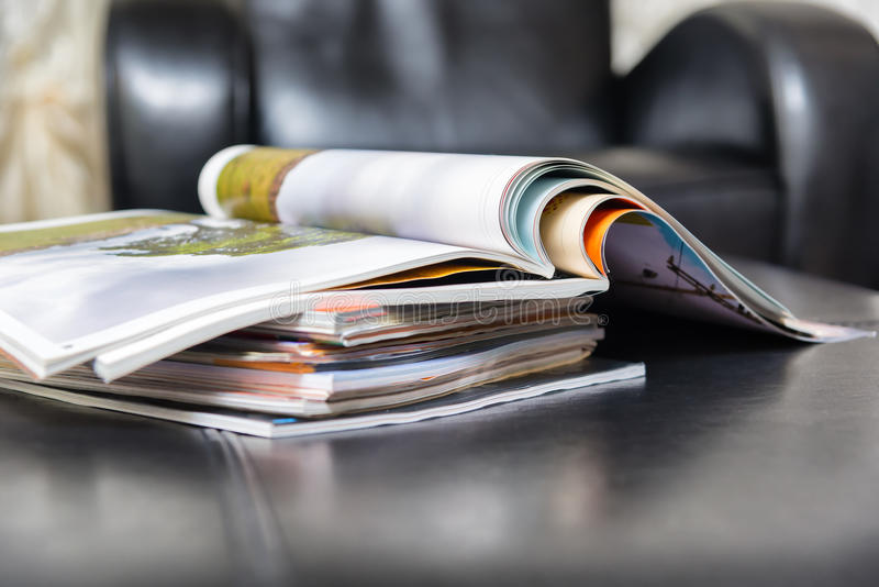 Pile of magazines at home. Color magazines in leather living room stock photos