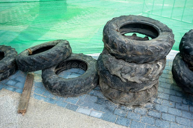 Pile of many old, used tires against green background stock photography