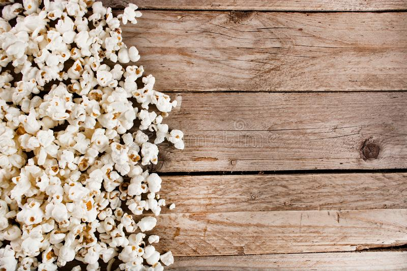 Spilled popcorn on wooden and retro desk. Pile many spilled popcorn on wooden and retro desk and space for design and text. Retro and vintage food concept. Close royalty free stock images