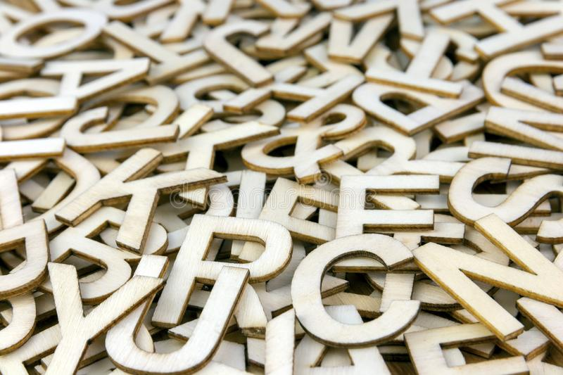 Pile of Mixed Wooden Letters Close Up. Pile of mixed wooden capital letters close up with a shallow depth of field royalty free stock image