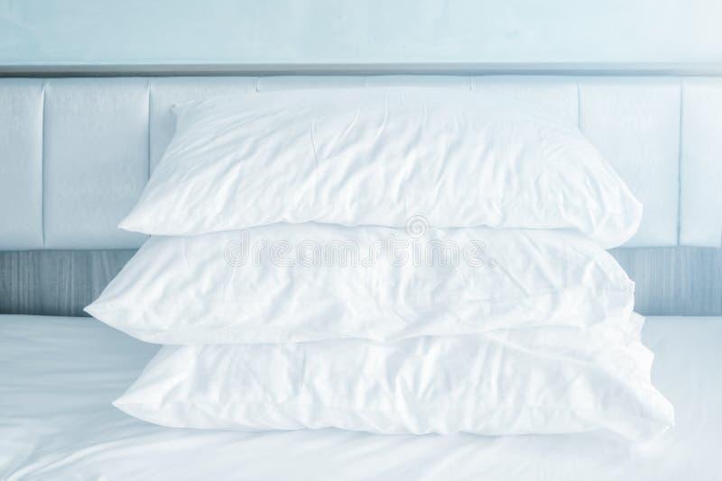 Pile molle confortable d'oreillers sur les draps blancs dans la pièce moderne de lit images stock