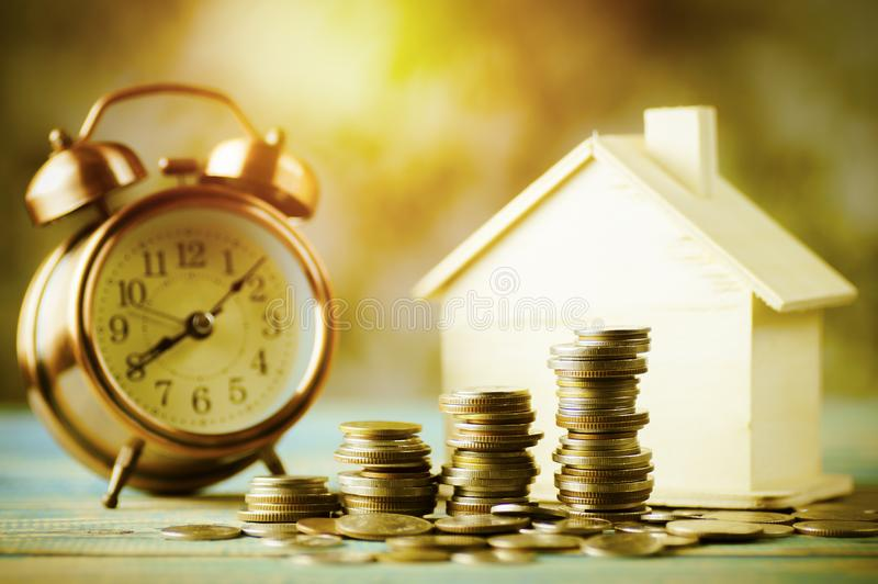 Pile of money, coins growing up with house wood and alarm clock, concept in business about loan, selling,finance, mortgage and bu. Ying home stock photo
